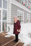 Cheerful elderly woman standing on the porch Stock Photography