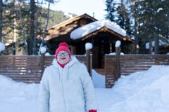 Cheerful elderly woman stands and smiles happily in front of a rustic wooden house among the snowdrifts in the forest royalty free stock photos