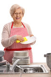 Cheerful elderly woman wiping plates. And looking at the camera isolated on white background Stock Photo
