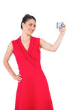 Cheerful elegant brunette in red dress taking picture Royalty Free Stock Images