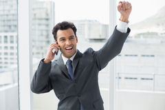 Cheerful elegant businessman using cellphone in office Royalty Free Stock Image