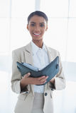 Cheerful elegant businesswoman holding her agenda Stock Photo