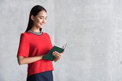 Cheerful elegant girl is enjoying her hobby. Joyful time. Positive stylish young asian woman is standing with favorite book and reading with pleasure. She is royalty free stock image