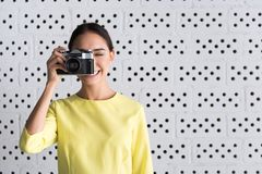 Cheerful elegant girl is taking photo. Photographer pose. Young attractive professional woman is standing in pose of making pictures while holding her camera and royalty free stock photo