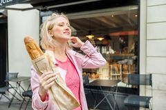Businesswoman with baguette. Cheerful elegant woman holding baguette in rue Lepic in Montmartre, Paris, France. Caucasian blonde businesswoman with traditional Royalty Free Stock Photo