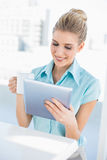 Cheerful elegant woman using tablet holding coffee Stock Photos
