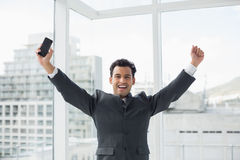 Cheerful elegant young businessman cheering in office Royalty Free Stock Image