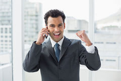 Cheerful elegant young businessman using cellphone in office Royalty Free Stock Image