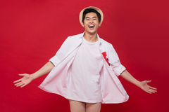 Cheerful elegant young handsome asian man over red background. C Royalty Free Stock Images