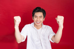 Cheerful elegant young handsome asian man over red background. C Stock Photo