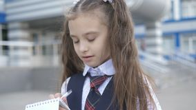Cheerful elementary school Student in school uniform writes or draws something in a notebook near the school building.