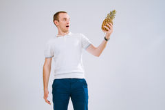 Cheerful and emotional guy holding a pineapple in his hand on a white background. A guy in a white T-shirt with a pineapple in his hands is emotionally looking Stock Photography