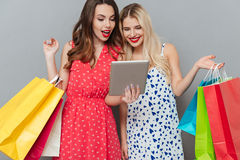 Cheerful emotional ladies friends with shopping bags and tablet. Image of cheerful emotional young two ladies friends with bright makeup lips standing over grey Royalty Free Stock Photo