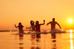 Euphoric friends swimming in evening royalty free stock photo
