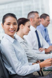Cheerful employee attending presentation with her colleagues Royalty Free Stock Photos