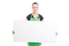 Cheerful employee with green apron holding blank billboard Stock Photo