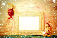 Cheerful empty photo frame Christmas card. Vintage Santa Claus rag doll and reindeer climbed on a ladder drawn by a child stock photos