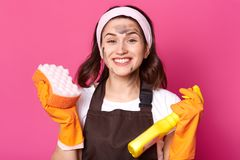 Cheerful energetic bright young woman looks happy  over pink background in studio, ready to do general cleaning, stain her. Face while tiding up, wearing stock photography