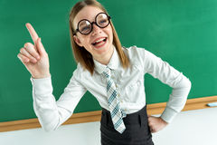 Cheerful enthusiastic pupil pointing with her finger up, telling the teacher know something Royalty Free Stock Photography