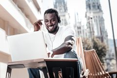 Cheerful entrepreneur having business call outdoors. Work is calling. Low angle of a friendly looking African American guy smiling cheerfully while talking to Royalty Free Stock Photography