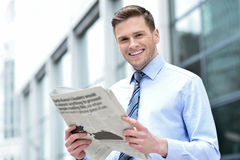 Cheerful entrepreneur reading newspaper Stock Photo