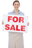 Cheerful estate agent posing with for sale sign. Against white background Stock Images