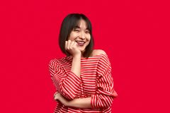 Cheerful ethnic lady supporting cheek. Pretty Asian woman in trendy striped outfit smiling and supporting cheek with hand against vivid red background royalty free stock photography