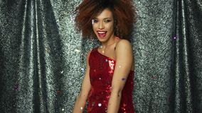 Ethnic woman throwing up confetti. Cheerful ethnic woman in glamour red dress looking at camera and throwing up colorful glittering confetti in studio stock video