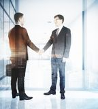 Deal concept. Cheerful european businessmen shaking hands in abstract office interior with city view. Deal concept. Double exposure Stock Images