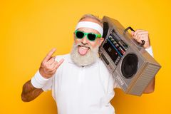 Cheerful excited aged funny active athlete cool pensioner g. Randpa in eyewear with bass clipping ghetto blaster recorder. Old school, swag, sticking tongue royalty free stock photography