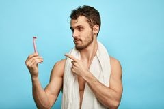 Cheerful excited awesome sexy happy handsome guy holding a shaver stock photography