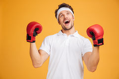 Cheerful excited man boxer in gloves shouting and celebrating success Royalty Free Stock Photo