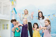 Excited mothers having fun with kids at birthday party royalty free stock photo