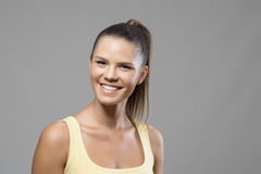 Cheerful excited sporty woman with perfect toothy smile looking at camera. Over gray studio background Royalty Free Stock Images
