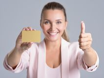 Cheerful excited surprised young woman with credit card over white background. Cheerful excited surprised young woman with credit card and thumb up over white stock photography