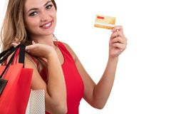 Cheerful excited surprised young woman with credit card over white background.  Stock Photo