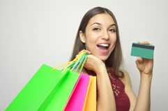 Cheerful excited surprised young woman with credit card and shopper bags over white background stock photography