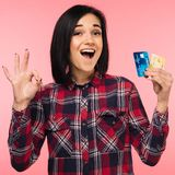Cheerful excited surprised young woman with credit card showing sing ok over pink background royalty free stock photos