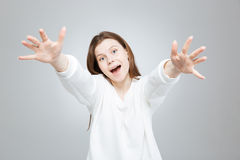Cheerful excited teenage girl smiling and reaching hands. Over gray Royalty Free Stock Images