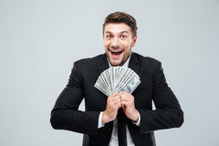 Cheerful excited young businessman laughing and holding money Royalty Free Stock Photography