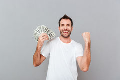 Cheerful excited young man holding dollars and celebrating success. Over gray background Stock Images