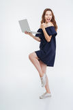 Cheerful excited young woman holding laptop and celebrating success royalty free stock image