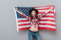 Cheerful excited young woman holding USA flag and looking away Stock Photos