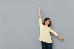 Cheerful excited young woman with raised hands standing and shouting Stock Images