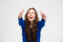 Cheerful excited young woman reaching hands to camera Stock Photos