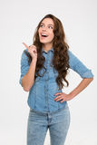 Cheerful excited young woman standing and pointing away. Cheerful excited young woman in jeans shirt standing and pointing away over white background Royalty Free Stock Images