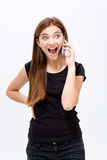 Cheerful excited young woman talking on cell phone. Over white background Stock Photography