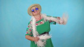 Cheerful expressive energetic old woman in a hat and boa dancing on a blue background. Cheerful expressive energetic old woman with glasses in a hat and boa stock video