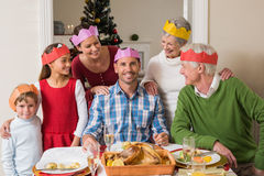 Cheerful extended family in party hat at dinner table Royalty Free Stock Images