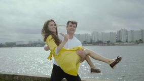 Smiling young woman and man dance funny dance on a dock in a rainy weather stock video footage